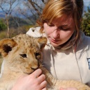 A girl taking girl of a lion cub