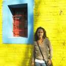 A girl having her picture taken in front of the bright yellow wall