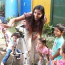 A girl showing the children how to take video