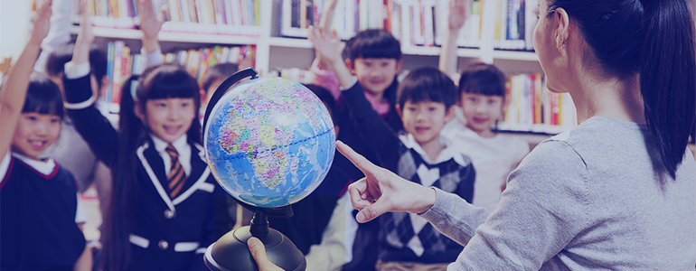 ESL teacher pointing at a globe for the students