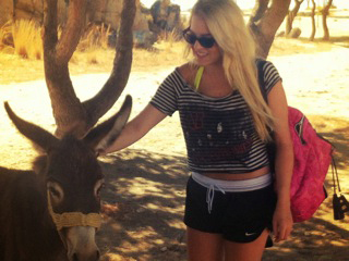 Girl petting a donkey in Greece