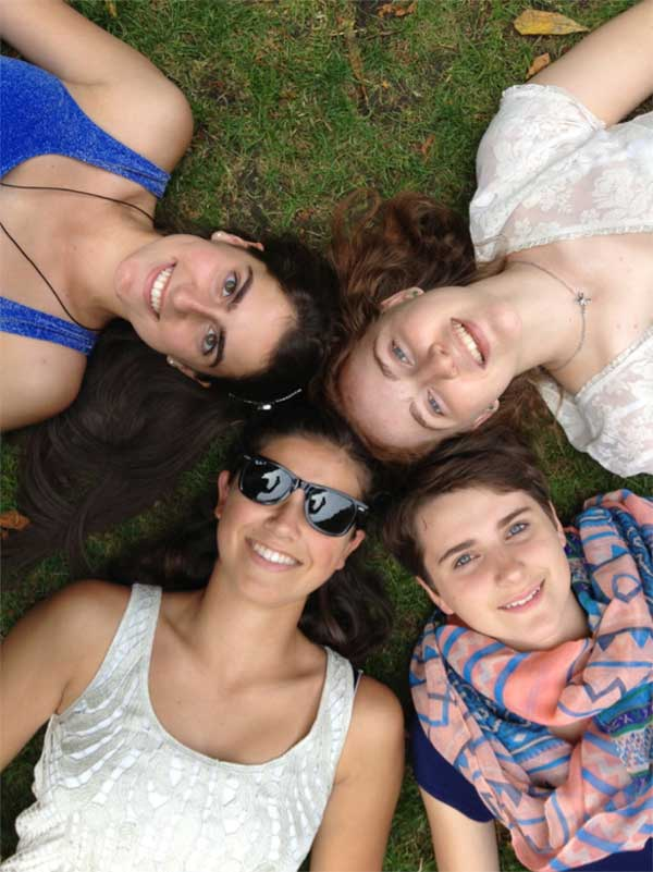 Female friends lying in a grassy area