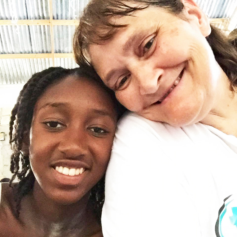 A volunteer in Haiti with a local teen