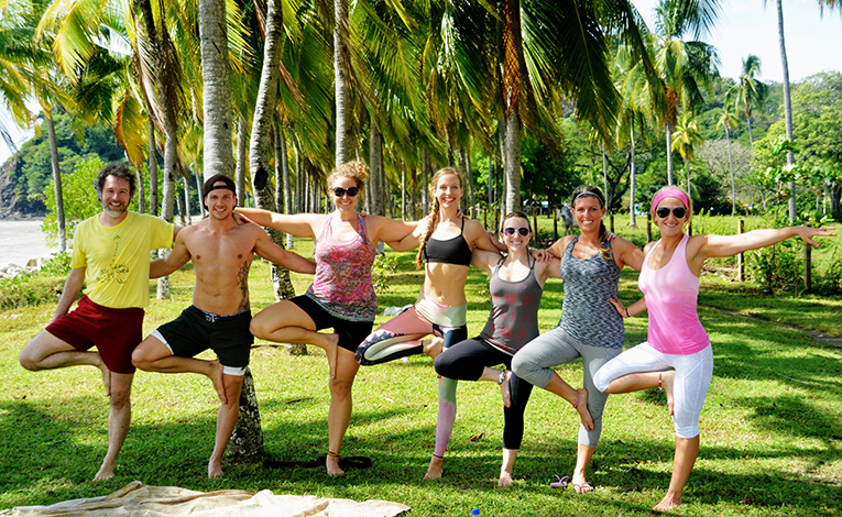 Students doing yoga on a beach in Costa Rica