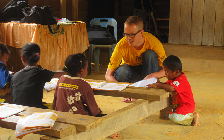 Volunteer talking to children at a community center in Southeast Asia