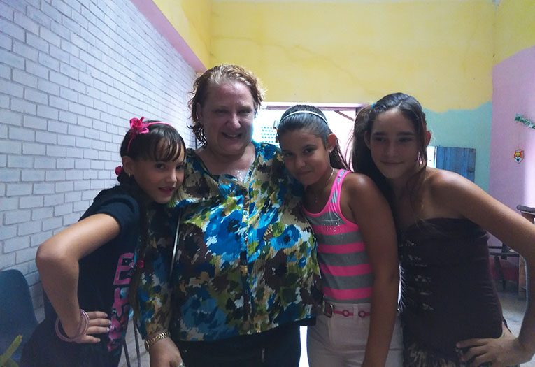 Volunteer teacher with local students in Cuba
