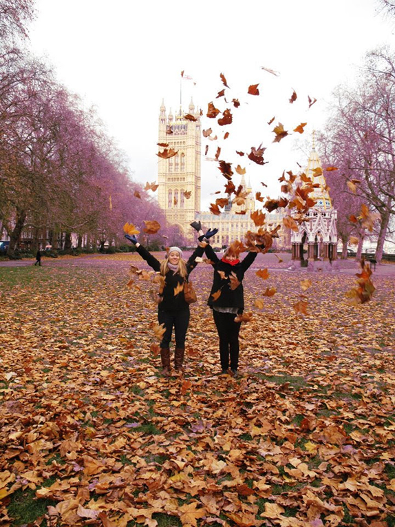 Girls throwing leaves in the air in a park in London