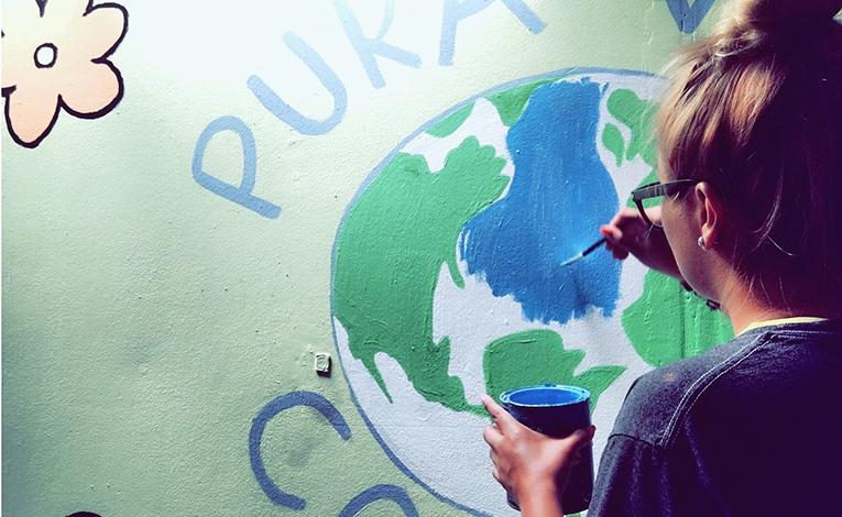 Volunteer painting a mural in Costa Rica