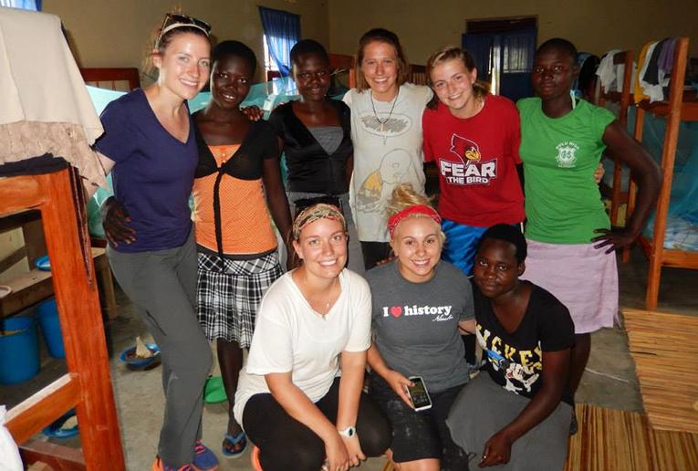 Volunteers and local teens in a dorm room in Uganda