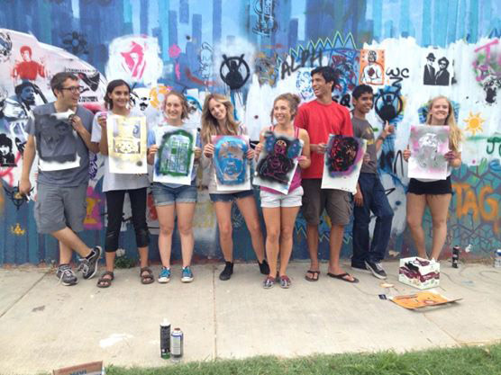 Students holding stenciled street art in Mexico