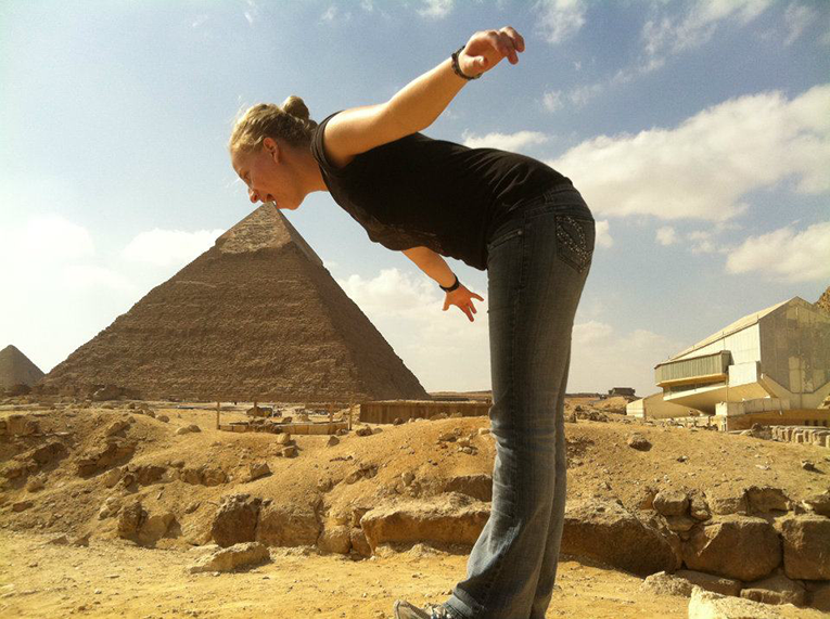 Tourist posing with the pyramids in Egypt