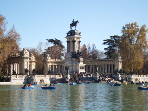 Summer day at Parque del Retiro. People are renting rowboats and relaxing in front of the famous monument of Alfonso XII.