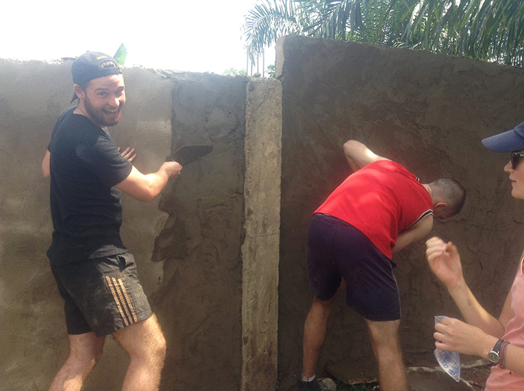 Construction volunteers plastering a wall in Ghana