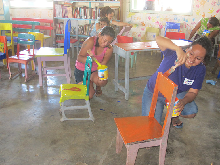 Volunteers in Belize painting chairs for children