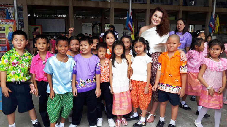 International teacher and her students in traditional Thai clothes