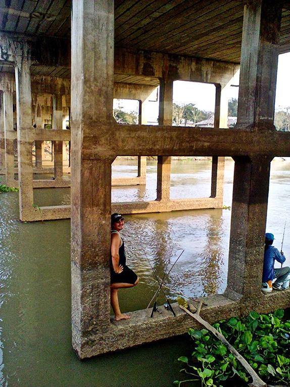 Man standing under a pier in Thailand