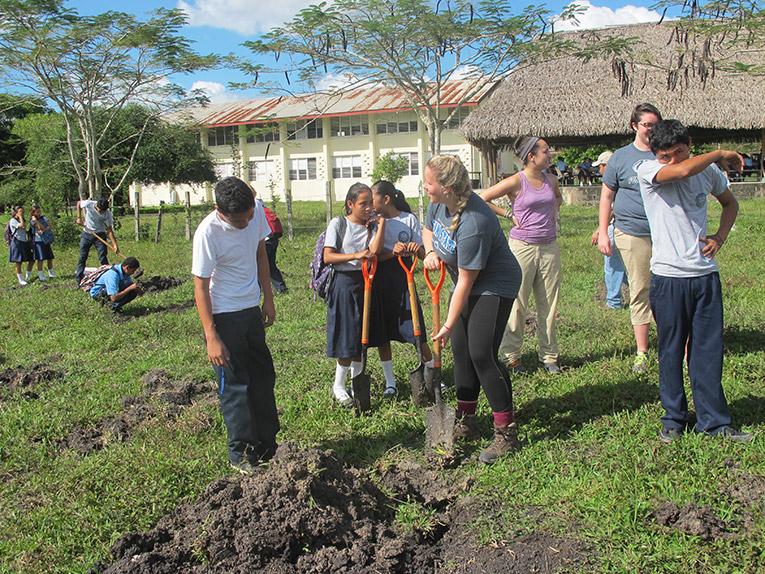Volunteer building a school garden in Belize with local children