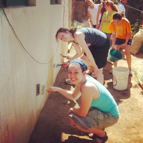 volunteers helping reconstruct the building by painting