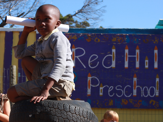 A child sitting on a tire at his Preschool