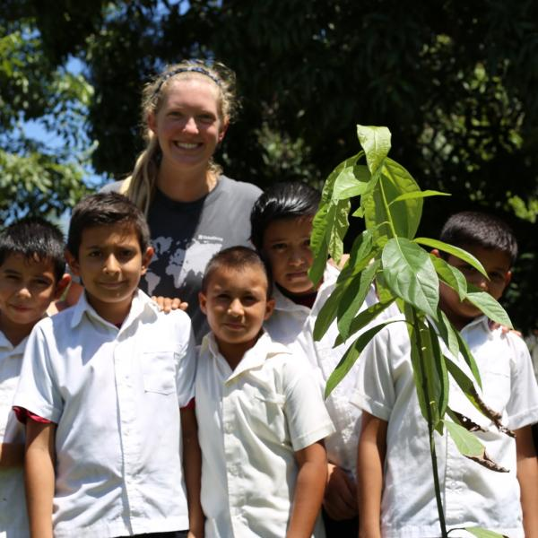FTPF volunteer helping school kids plant a cacao tree