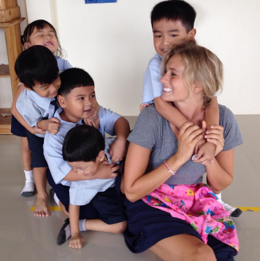 Teacher giving piggyback rides to children