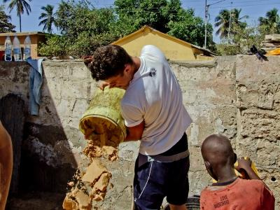 Projects Abroad volunteer mixing concrete with a local child. St. Louis, Senegal