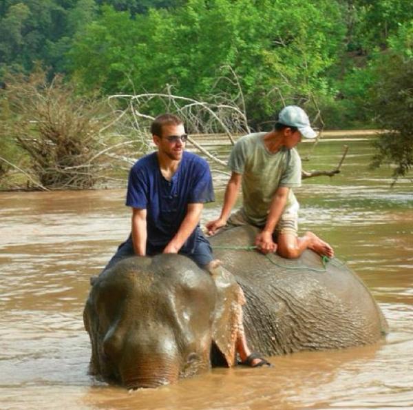 A volunteer riding an elephant