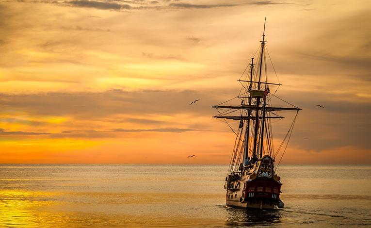 Ship sailing into the horizon at sunset.