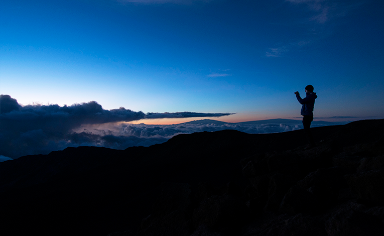 Person taking a photo of mountains at sunset