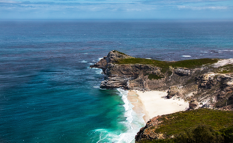 The rocky cliffside of the cape of good hope looking out on blue ocean waters