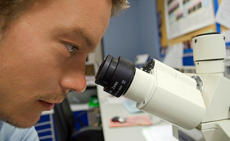 Man looking through the lens of a microscope