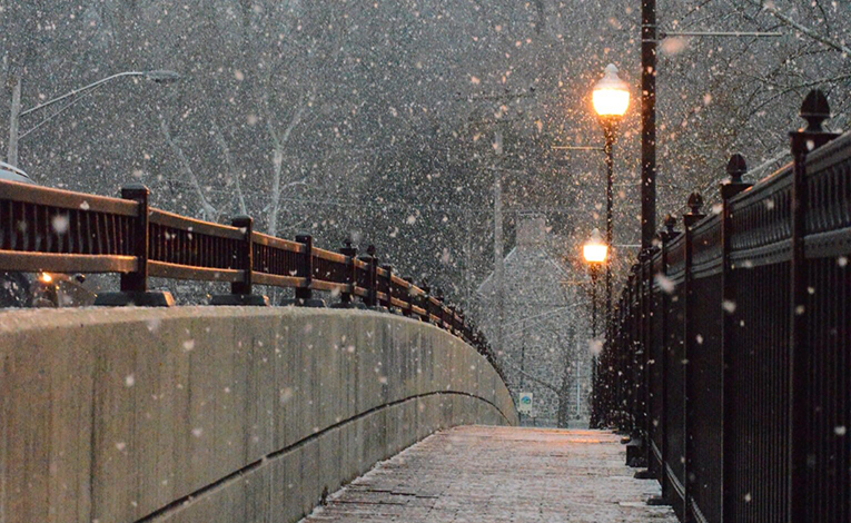 Walkway lit by streetlamps in the snow