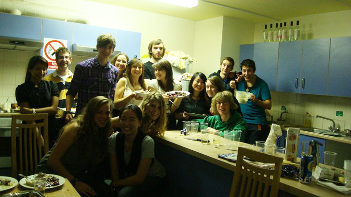 Students crowded around a kitchen counter eating food