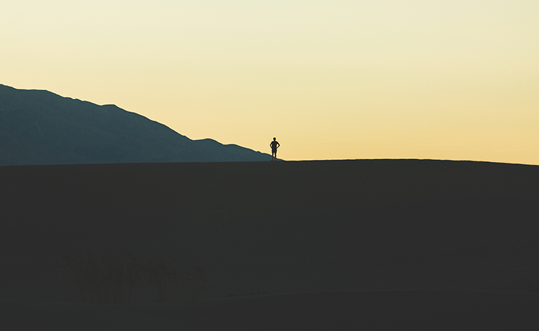 Silhouette of a man standing on a bright horizon