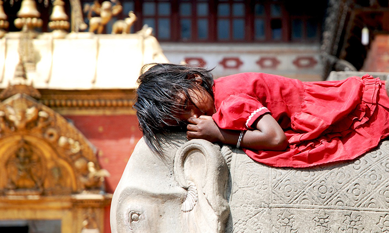 A Nepalese girl lying on an elephant statue