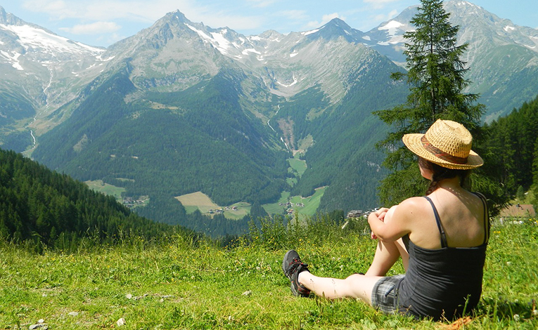 A woman sitting in the grass in the Alps