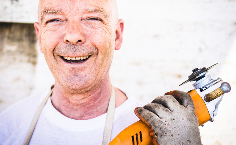 smiling older man with power saw in his hand