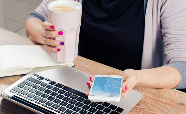 Woman drinking coffee and checking her cell phone
