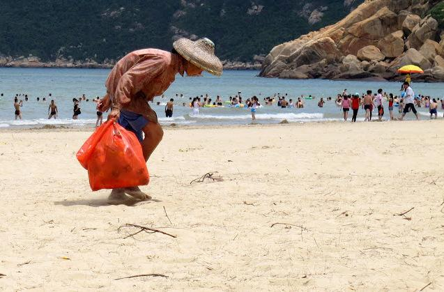 Woman looking for recyclable materials at a beach in China