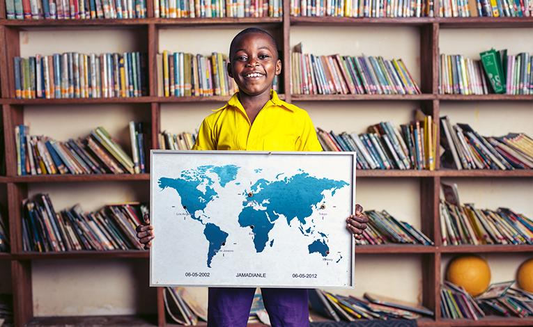 A boy holding a world map