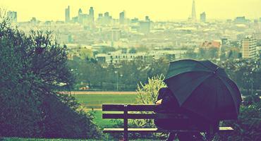A couple enjoys rainy romance on Parliament Hill in Hampstead Heath.