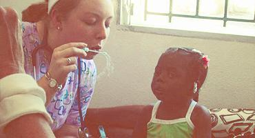 A volunteer blows bubbles to entertain a young Haitian child