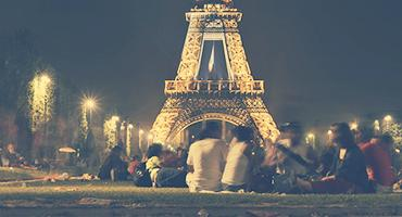 Students sitting in front of the Eiffel Tower in Paris, France