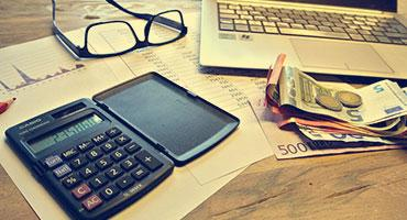 Items such as laptop, documents with charts, money and calculator on a table.