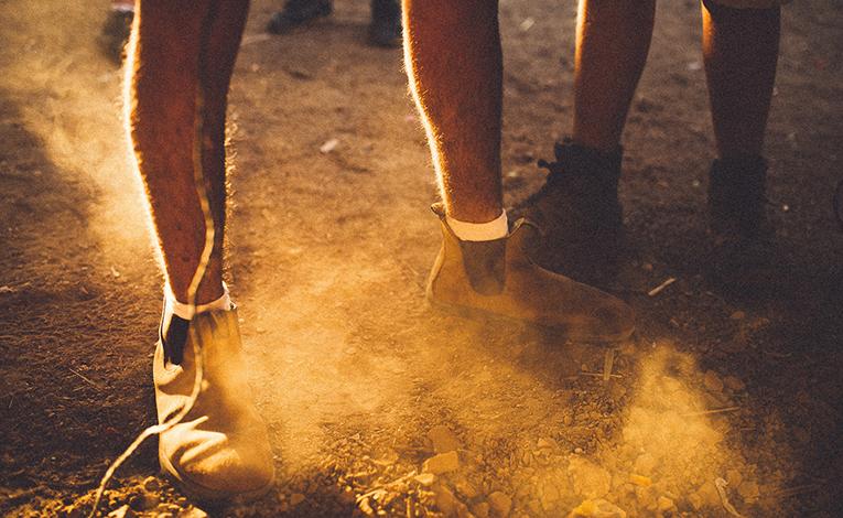 Dust churning over mens feet