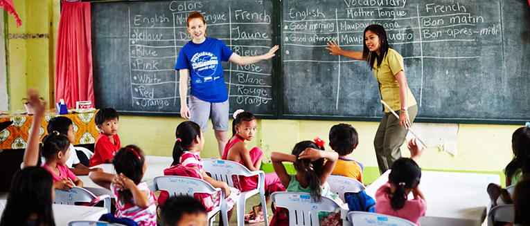 A volunteer teaching in the Philippines with a local teacher