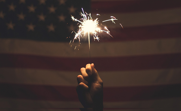 Hand holding a sparkler against the backdrop of an American flag