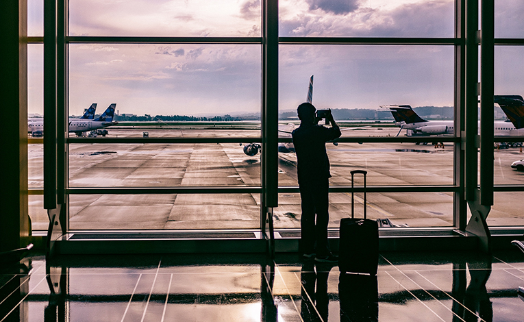 Silhouette of a man and a suitcase at an airport