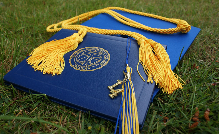 Blue graduation cap and diploma with bright yellow cords and tassel
