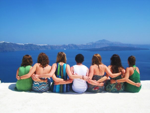 Female students sitting along a coastline